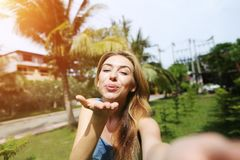 Frohe Frau schicken Luftkuß zum comera, welches das selfie nimmt und reisen nach sonniges Thailand mit Palmen und grünem Gras Lizenzfreie Stockfotos