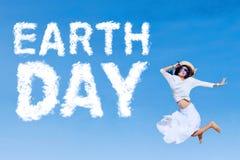 Frohe Frau springt mit Tag der Erde-Text Stockbild