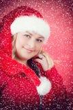 Frohe Frau in Weihnachtsmann-Hut mit Schneeflocken Stockfoto