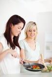 Frohe Frauen, die Abendessen kochen Lizenzfreie Stockbilder