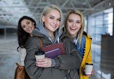 Frohe Frauen, die Getränk und Notizbücher halten Lizenzfreie Stockfotos