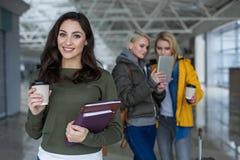 Frohe Frauen, die im Anschluss mit Getränk und Büchern aufwerfen Lizenzfreies Stockbild