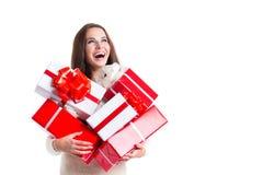 Frohe Frauenfrau, die viele Kästen mit Geschenken auf einem weißen Hintergrund hält Lizenzfreie Stockbilder