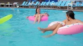 Frohe Freundinnen, die auf aufblasbarem Ring und Matratze im Pool, Sommerrest von schönen Mädchen in den Badeanzügen schwimmen stock video