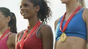 Frohe gemischtrassige Mädchen, die auf dem Podium, Medaillen auf Kästen stolz zeigend stehen stock video