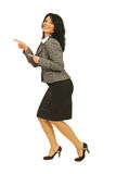 Frohe Geschäftsfrau, die auf linkes Teil zeigt Stockfotos