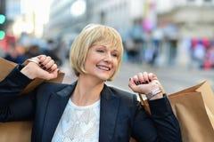 Frohe Geschäftsfrau, die Einkaufstaschen hält Lizenzfreies Stockfoto