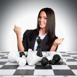 Frohe Geschäftsfrau gewinnt Schach und hob seins an Stockfoto