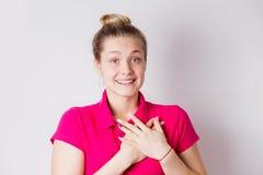 Frohe glückliche junge Frau lächelt aufgeregt, ist überrascht und Hände auf Herzen auf weißem Hintergrund hält Positive Gefühle,  stockfotos