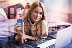 Frohe glückliche Frau, die Ihnen ihren Smartphone zeigt Stockbilder