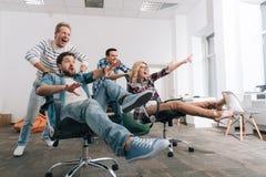 Frohe glückliche Menschen, die in den Bürostühlen sitzen Lizenzfreie Stockfotos