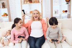 Frohe Großmutter mit den netten Enkelkindern, die auf der Spielkonsole sitzt auf Couch spielen Stockbilder