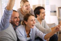 Frohe Gruppe Freunde, die Fußballspiel aufpassen Lizenzfreies Stockbild