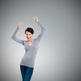 Frohe hübsche Frau legt ihre Hände mit zwei Fingern dar, die oben gezeigt werden Stockbild