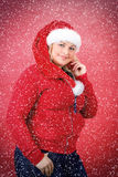 Frohe hübsche Frau in rotem Weihnachtsmann-Hut lächelnd mit Schneeflocken Lizenzfreie Stockfotos