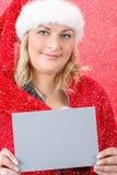 Frohe hübsche Frau in rotem Weihnachtsmann-Hut lächelnd mit Schneeflocken Lizenzfreie Stockbilder