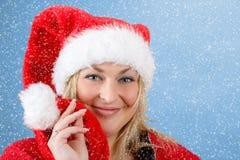 Frohe hübsche Frau in rotem Weihnachtsmann-Hut lächelnd mit Schneeflocken Stockfoto