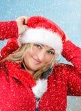 Frohe hübsche Frau in rotem Weihnachtsmann-Hut lächelnd mit Schneeflocken Stockbild