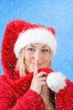 Frohe hübsche Frau in rotem Weihnachtsmann-Hut lächelnd mit Schneeflocken Lizenzfreie Stockfotografie