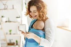 Frohe hübsche Mutter mit dem schlafenden Sohn im Babyriemen, Tasse Tee und Lachen in der Hand halten plaudernd mit ihrem Besten lizenzfreie stockbilder