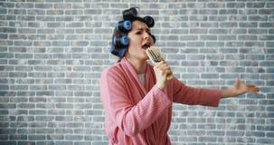Frohe Hausfrau mit Haarrollen singend im Haarbürstetanzen, das Spaß hat stock video footage