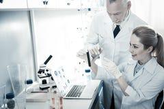 Frohe intelligente Biologen, die den Prüfling betrachten Stockbilder