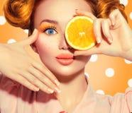 Frohe Jugendliche der Schönheit nimmt saftige Orangen Jugendlich vorbildliches Mädchen mit Sommersprossen, lustiger roter Frisur, stockfotografie