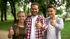 Frohe Jugendliche und ihr Vater, die Daumen oben in Kamera am Park, Familie zeigt lizenzfreie stockfotos