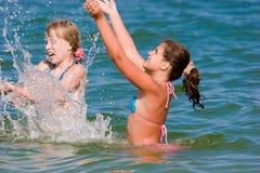 Frohe Jugendlichmädchen, die am Meerwasser spielen Lizenzfreie Stockbilder