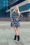 Frohe junge blonde Frau im Mantel, der Kamera und smili betrachtet Lizenzfreie Stockbilder