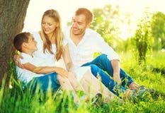 Frohe junge Familie, die Spaß draußen hat Lizenzfreie Stockbilder
