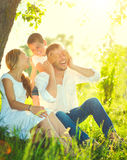 Frohe junge Familie, die Spaß draußen hat stockbild
