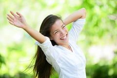 Frohe junge Frau, die Arme im Park anhebt Stockbilder