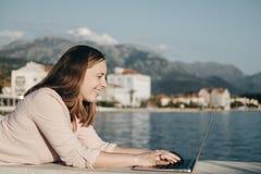 Frohe junge Frau, die auf Damm liegt und an Laptop arbeitet VA Stockfotografie