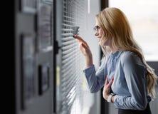 Frohe junge Frau, die durch Fenster Jalousie schaut stockfotos