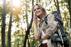 Frohe junge Frau, die durch Mobiltelefon im Wald spricht Stockfotos