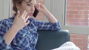 Frohe junge Frau, die zu Hause am Handy spricht stock footage