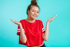 Frohe junge Frau im roten sportlichen T-Shirt ihre Schultern zuckend lizenzfreie stockfotografie