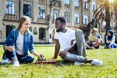 Frohe junge Leute, die draußen Schach spielen stockfotografie