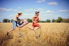 Frohe junge Paare, die Spaß auf dem Weizengebiet haben Aufgeregter Mann und Frau, die mit Retro- ledernem Koffer auf blauem Himme Stockfotos