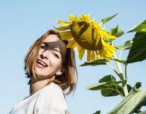Frohe kaukasische Frau, die mit gelber Sonnenblume aufwirft Lizenzfreie Stockfotos