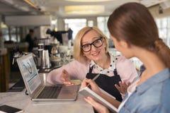 Frohe Kellnerin, die Arbeit mit ihrem Arbeitgeber bespricht Lizenzfreie Stockfotografie