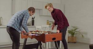 Frohe Kerle, die foosball in der Dachbodenwohnung spielen stock footage
