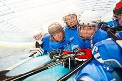 Frohe Kinder in der Hockeyuniform, die auf Eisbahn legt lizenzfreie stockfotos