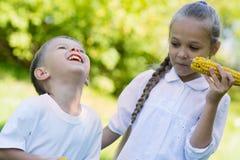 Frohe Kinder, die draußen Mais essen Stockfotos