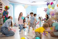 Frohe Kinder und ihre Eltern unterhalten und haben Spaß mit Farbballon auf Geburtstagsfeier stockbilder