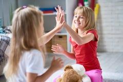 Frohe kleine Mädchen, die zusammen spielen Lizenzfreies Stockfoto