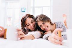 Frohe lächelnde junge Frauen des Porträts zwei, die auf Bett mit Tassen Tee kühlen In der modernen Wohnung morgens aufwachen lizenzfreies stockfoto