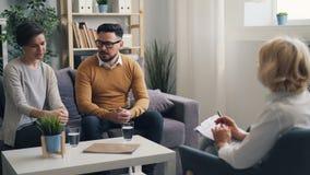 Frohe lächelnde Unterhaltung des Paarmannes und -frau mit Psychotherapeuten während der Beratung stock video