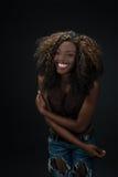 Frohe lachende Afroamerikanerfrau gegen einen dunklen Hintergrund Stockbild